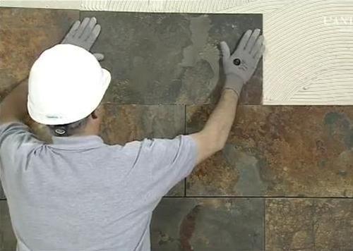Полагане на естествен камък на стената